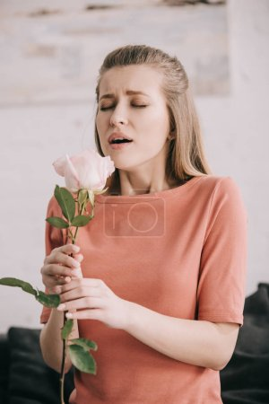 beautiful blonde girl with pollen allergy sneezing with closed eyes while holding rose at home