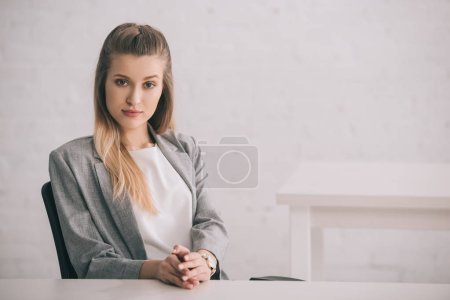 Photo for Attractive blonde woman sitting with clenched hands and looking at camera - Royalty Free Image