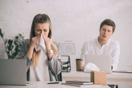Photo for Blonde businesswoman sneezing in tissue near coworker in office - Royalty Free Image