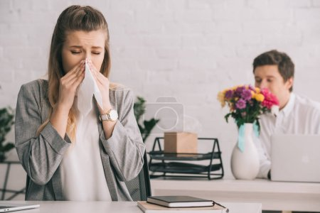 Foto de Rubia empresaria con polen alergia estornudo tejido cercano compañero de trabajo que huele a flores en oficina - Imagen libre de derechos