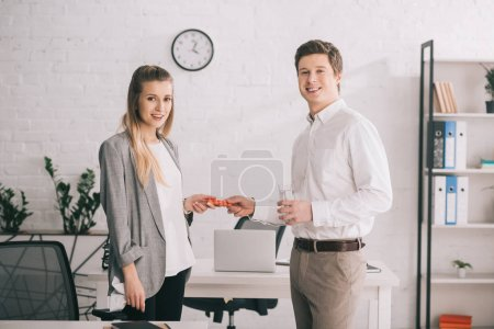 Photo for Happy businessman holding pills and glass of water near cheerful blonde colleague in office - Royalty Free Image