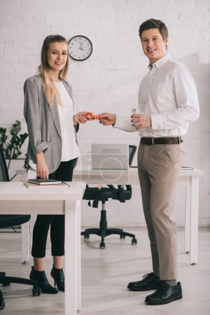 Photo for Cheerful businessman holding pills and glass of water near happy blonde colleague in office - Royalty Free Image