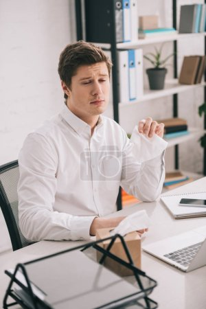 Photo for Sad businessman holding tissue while sitting near laptop in office - Royalty Free Image