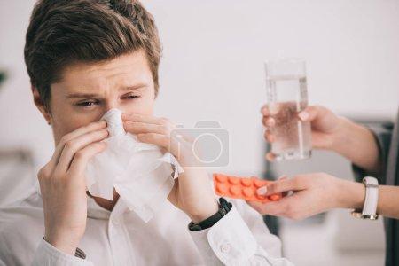 Photo pour Vue recadrée de la femme tenant des pilules et un verre d'eau près d'un collègue éternuer dans les tissus - image libre de droit
