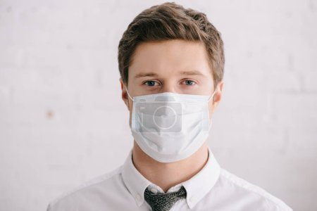 Photo for Man in suit and medical mask looking at camera - Royalty Free Image