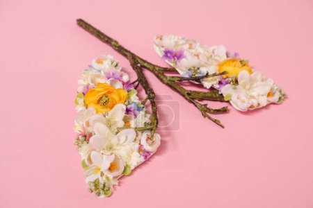 floral composition with blooming flowers and twigs in shape of lungs on pink
