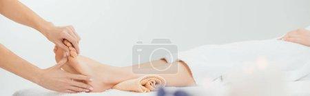 plano panorámico de masajista haciendo masaje de pies a mujer adulta en spa