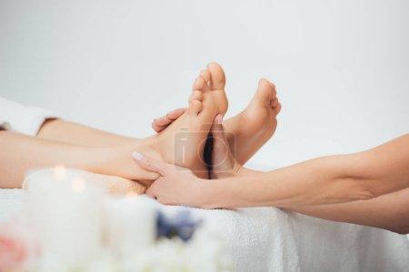Photo pour Focus sélectif de masseur faire massage des pieds à la femme adulte dans le Spa - image libre de droit