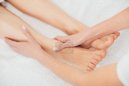 Photo pour Vue recadrée du masseur faisant massage des pieds à la femme adulte dans le spa - image libre de droit