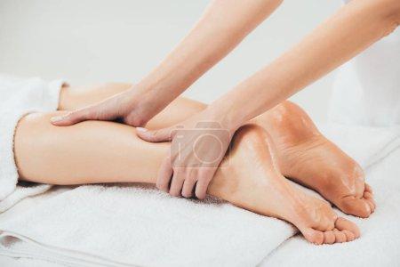 Photo pour Vue partielle du masseur faisant le massage de pied à la femme adulte dans le Spa - image libre de droit