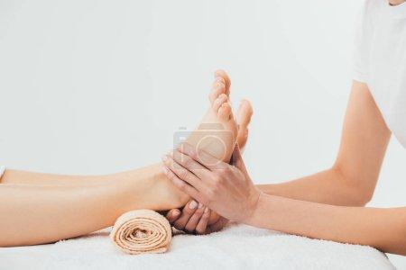 Photo pour Vue partielle du masseur faisant massage des pieds à la femme adulte dans le spa - image libre de droit