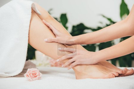 Photo for Partial view of masseur doing foot massage to adult woman in spa - Royalty Free Image