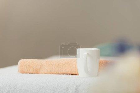 Photo pour Foyer sélectif de tasse blanche et serviette beige dans le spa - image libre de droit