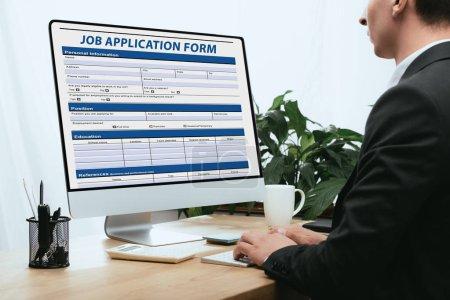 Photo pour Vue recadrée de l'homme remplissant le formulaire de demande d'emploi concept de carrière - image libre de droit