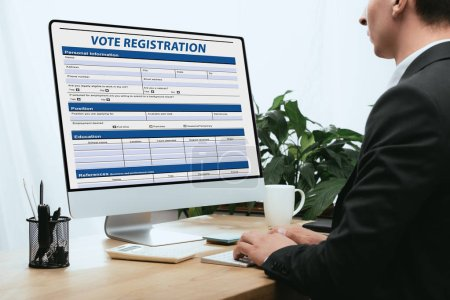 Photo pour Vue recadrée de l'homme remplissant Demande d'enregistrement de vote Concept électoral - image libre de droit