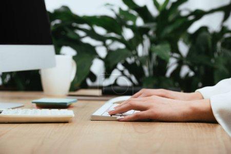 Photo pour Vue recadrée de la dactylographie de femme adulte sur le clavier d'ordinateur - image libre de droit