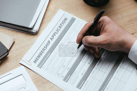 Photo pour Vue recadrée de l'homme remplissant le formulaire de demande d'adhésion Register Concept - image libre de droit