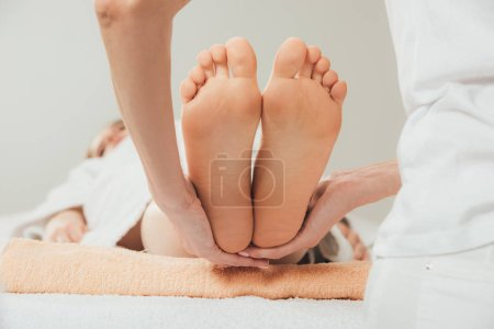 Photo for Cropped view of masseur doing foot massage to adult woman in spa - Royalty Free Image