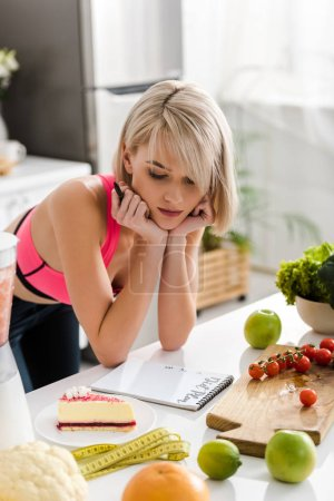 Photo for Attractive blonde woman in sportswear looking at cake in kitchen - Royalty Free Image