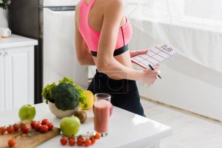 Foto de Vista recortada de mujer en ropa deportiva sosteniendo cuaderno con letras del plan en la cocina - Imagen libre de derechos