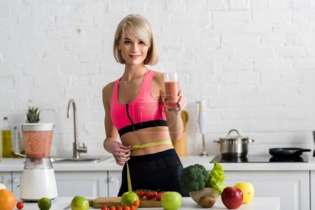 Photo for Cheerful sportswoman holding glass with smoothie and measuring tape in kitchen - Royalty Free Image