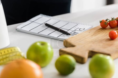 selective focus of wooden cutting board with cherry tomatoes near notebook with plan lettering