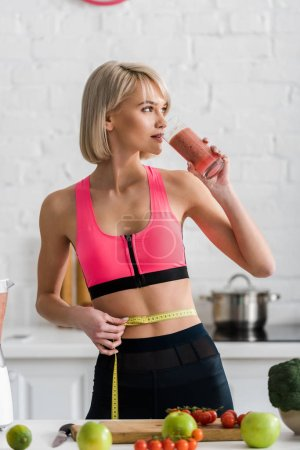 Photo for Blonde sportswoman drinking smoothie and holding measuring tape in kitchen - Royalty Free Image