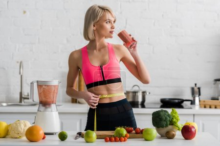 Photo for Blonde girl in sportswear drinking smoothie and holding measuring tape in kitchen - Royalty Free Image