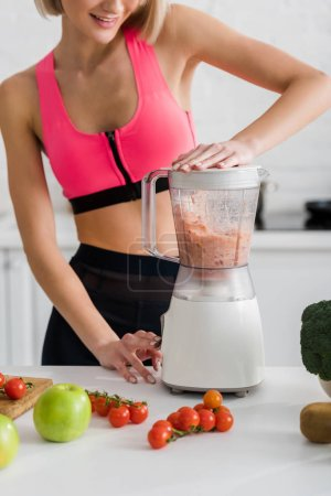 Photo for Cropped view of cheerful sportswoman preparing smoothie in blender - Royalty Free Image