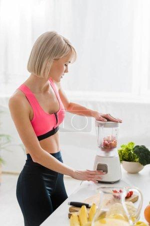 beautiful blonde sportswoman mixing food in blender