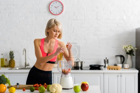 Photo for Beautiful blonde young woman in sportswear putting ingredients in blender - Royalty Free Image