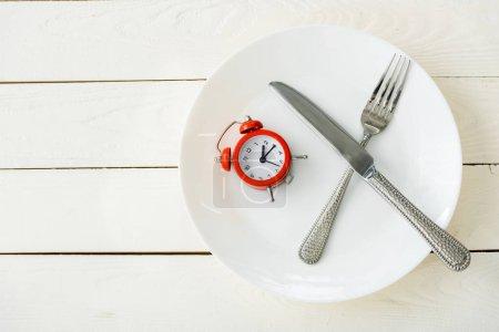 Photo pour Vue de dessus de la plaque blanche avec la coutellerie et le réveil rouge sur la surface en bois - image libre de droit