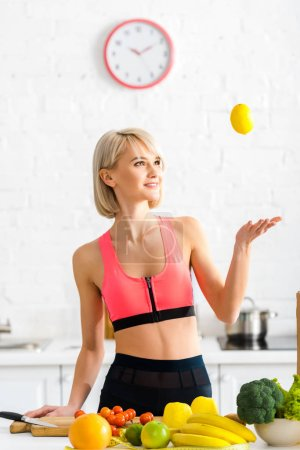 Photo for Cheerful blonde woman in sportswear catching lemon in kitchen - Royalty Free Image