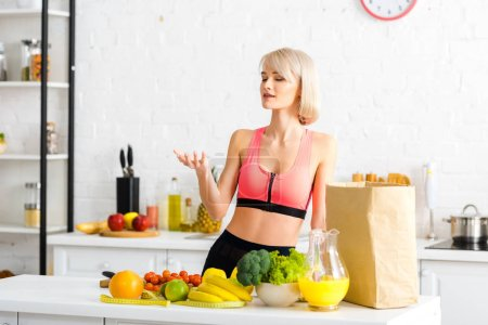 Photo for Beautiful blonde woman standing in kitchen near fruits and vegetables - Royalty Free Image