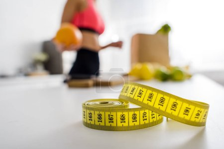 selective focus of yellow measuring tape near woman holding orange in kitchen