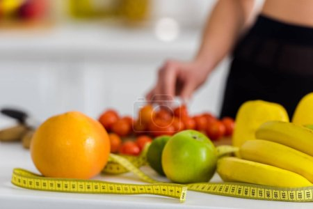 Photo for Cropped view of woman taking cherry tomato near measuring tape in kitchen - Royalty Free Image