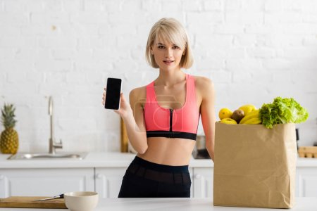 Photo for Blonde woman in sportswear holding smartphone with blank screen near paper bag with groceries - Royalty Free Image
