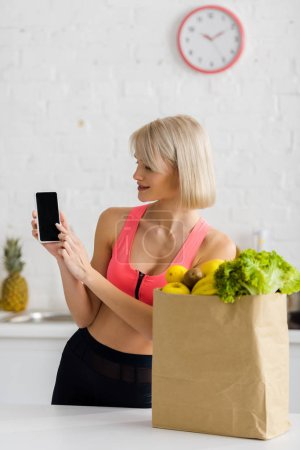 Photo for Cheerful blonde woman in sportswear holding smartphone with blank screen near paper bag with groceries - Royalty Free Image