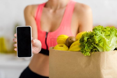 Photo for Cropped view woman in sportswear holding smartphone with blank screen near paper bag with groceries - Royalty Free Image