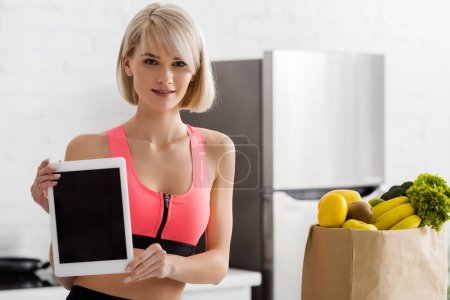 Photo for Blonde woman in sportswear holding digital tablet with blank screen near paper bag with groceries - Royalty Free Image