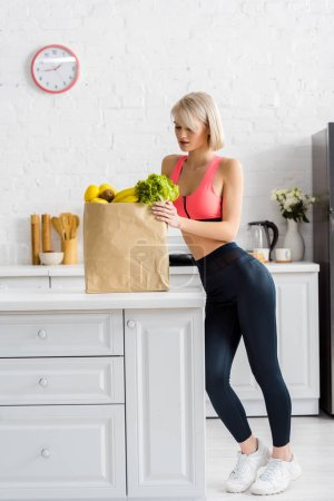 Photo for Attractive blonde woman in sportswear looking at paper bag with groceries - Royalty Free Image
