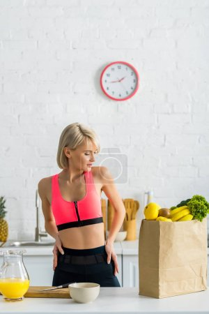 blonde woman in sportswear looking at paper bag with groceries in kitchen
