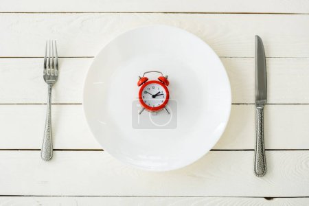 Photo for Top view of white plate with red alarm clock near cutlery on wooden surface - Royalty Free Image
