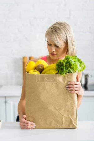 Photo for Blonde woman looking at paper bag with groceries in kitchen - Royalty Free Image