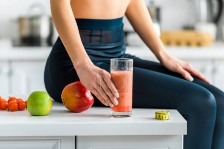 cropped view of woman holding glass of smoothie while sitting in kitchen near apples