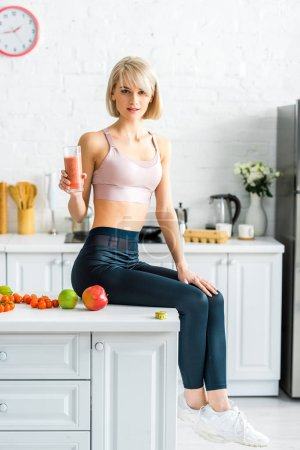 Photo for Attractive blonde girl in sportswear holding glass of smoothie while sitting in kitchen near apples - Royalty Free Image