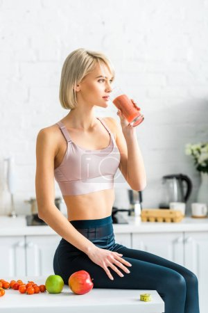attractive blonde girl in sportswear drinking tasty smoothie while sitting in kitchen near apples