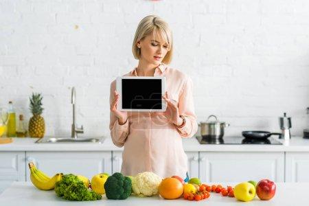 Photo pour Blonde femme enceinte tenant tablette numérique avec écran blanc près de la nourriture dans la cuisine - image libre de droit