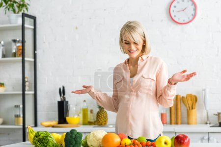 Photo for Cheerful blonde pregnant woman gesturing near fruits and vegetables - Royalty Free Image