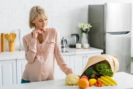 Photo for Blonde pregnant woman looking at tasty vegetables and fruits near paper bag - Royalty Free Image